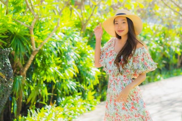 肖像画の屋外ガーデンビューの周りを幸せと歩いて美しい若いアジア女性