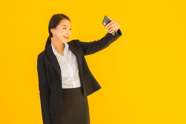 電話とコーヒーカップの美しい若いアジア女性の肖像画