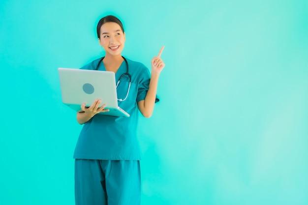 肖像画のラップトップまたはコンピューターを持つ美しい若いアジア医師女性