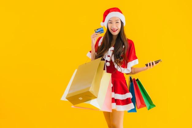 肖像画の美しい若いアジアの女性は多くの買い物袋でクリスマス服の帽子を着用します。