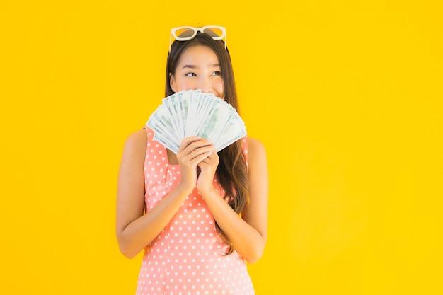 肖像画の多くの現金を持つ美しい若いアジア女性