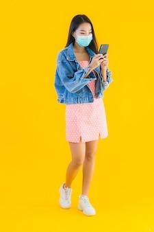 肖像画の美しい若いアジア女性着用マスク使用スマートフォン