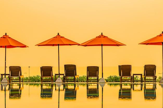 Прекрасный рассвет вокруг с зонтиком и стулом открытый бассейн