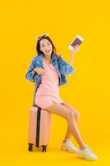 肖像画のパスポートと搭乗券と荷物旅行バッグを持つ美しい若いアジア女性