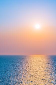 空の雲と海の海湾の周りの美しい夕日や日の出
