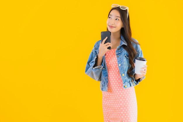 コーヒーカップとスマートフォンの肖像若い美しいアジアの女性
