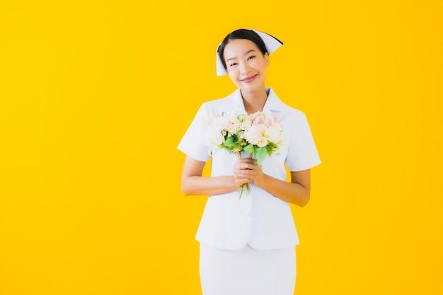 花と美しい若いアジア女性タイの看護師の肖像画