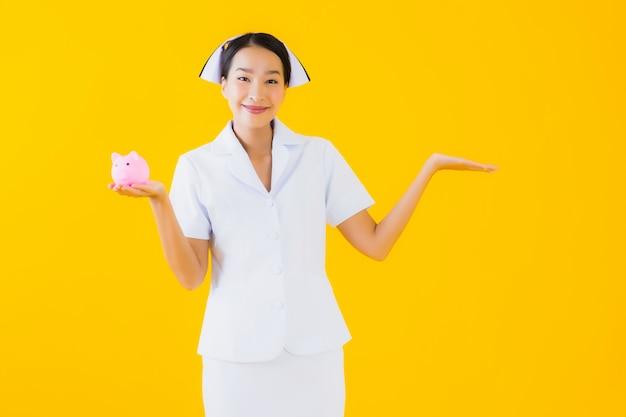 肖像画の多くの現金とお金を持つ美しい若いアジア女性タイの看護師