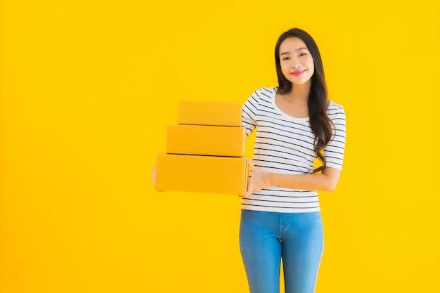 Женщина портрета красивая молодая азиатская с коробкой посылки готовой для грузить