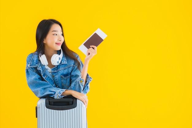 荷物バッグとパスポートを持つ若いアジア女性