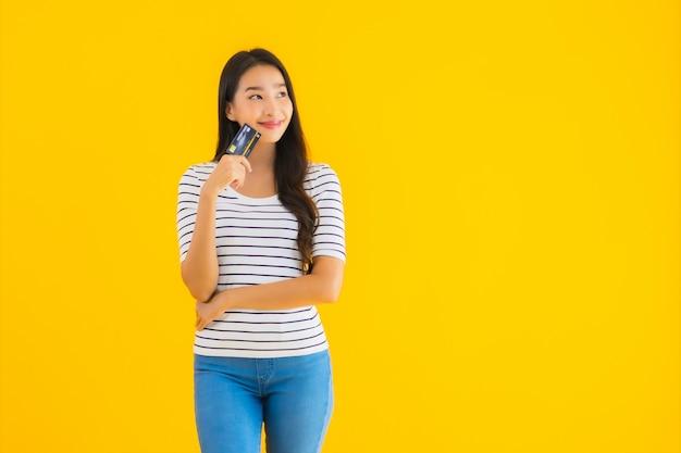 肖像画の美しい若いアジアの女性はクレジットカードを表示します。