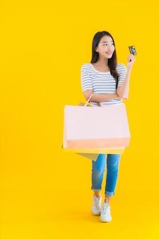 カラフルなショッピングバッグを持つ若いアジア女性
