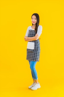 若いアジアの女性は幸せな笑顔でエプロンを着用