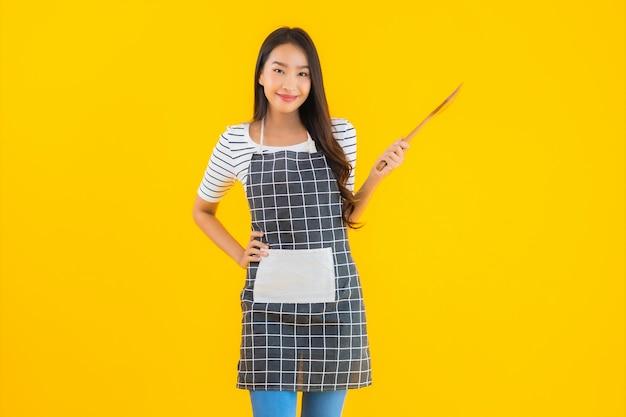 肖像画の美しい若いアジアの女性は黒い鍋とヘラでエプロンを着用します。