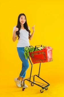Молодая азиатская женщина, делающая покупки продуктовый от супермаркета и тележки