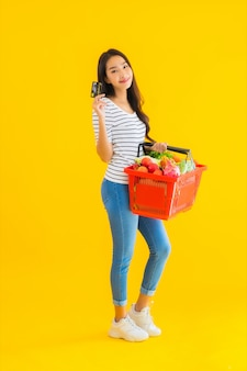 肖像画のバスケットの食料品やスーパーマーケットからカートの美しい若いアジア女性