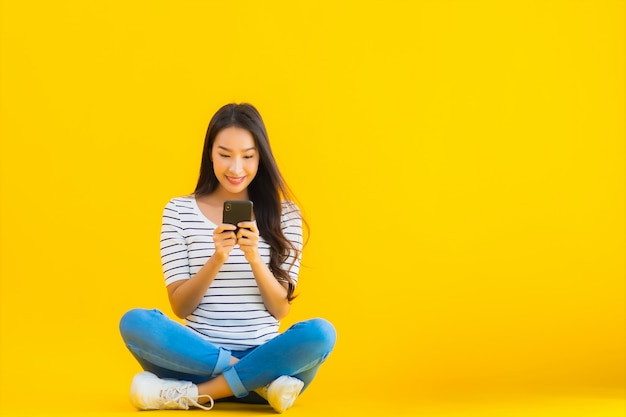若いアジア女性笑顔幸せな使用スマート携帯電話