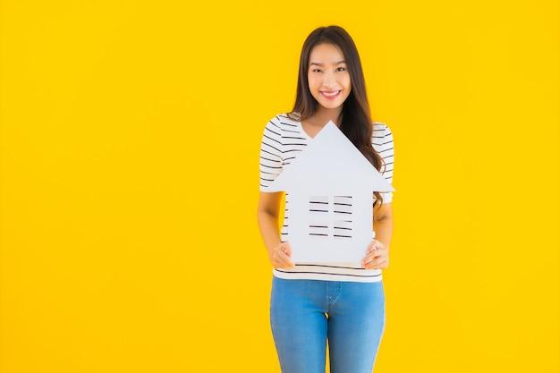 肖像画の美しい若いアジア女性は家の看板を表示