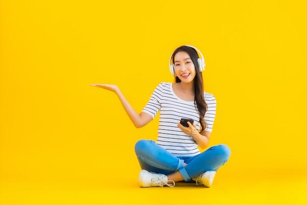 若いアジアの女性は、ヘッドフォンでスマートな携帯電話を使用します。