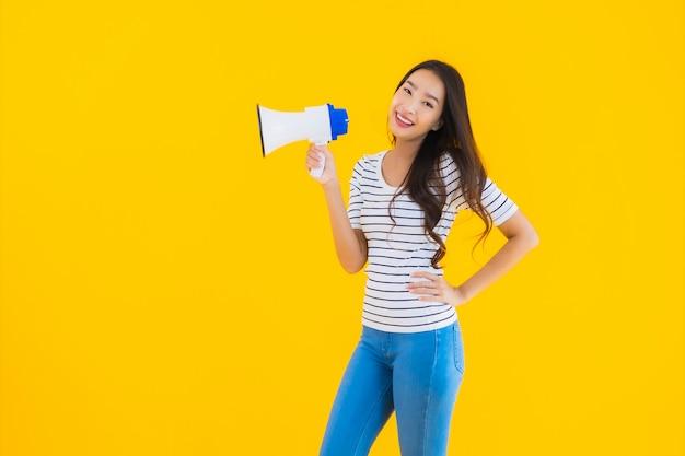 若いアジアの女性はメガホンを使用します