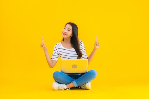 肖像画の美しい若いアジア女性はラップトップを使用します