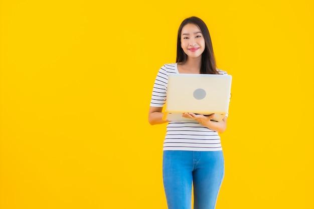 Молодая азиатская женщина использует ноутбук или ноутбук