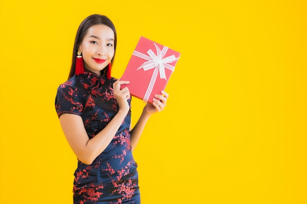 美しい若いアジアの女性の肖像画はチャイナドレスを着て、赤いギフトボックスを保持
