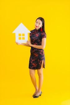 肖像画の美しい若いアジア女性はチャイナドレスショーの家の看板を着用します。