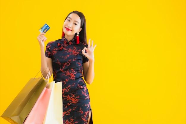 美しい若いアジアの女性の肖像画は買い物袋でチャイナドレスを着ています。