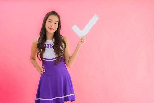 肖像画の美しい若いアジア女性チアリーダー笑顔ショーサイン