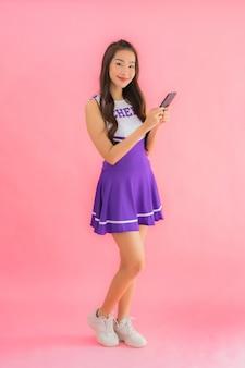 肖像画の美しい若いアジア女性チアリーダー使用スマート携帯電話