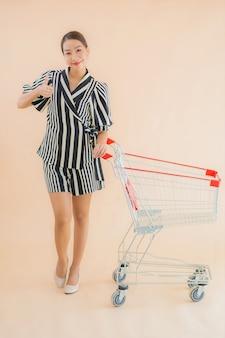 ショッピングカートと美しい若いアジア女性の肖像画