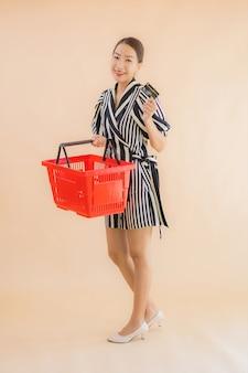 Женщина портрета красивая молодая азиатская с корзиной для товаров