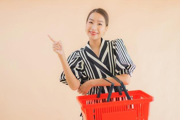ショッピングバスケットと美しい若いアジア女性の肖像画