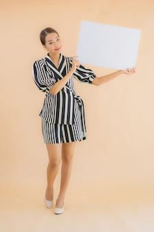 肖像画の美しい若いアジア女性は空の白い看板紙を表示します。