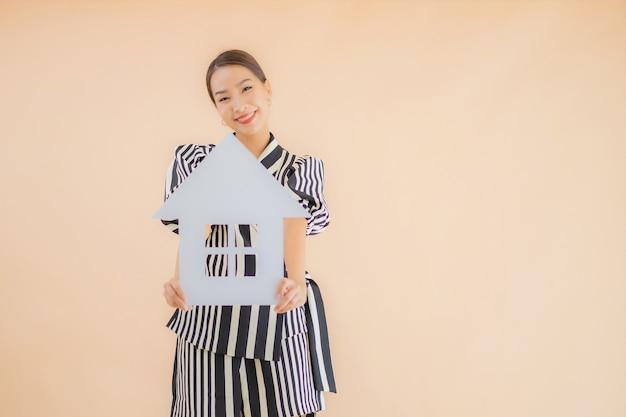 肖像画の美しい若いアジア女性は家や家の紙の看板を表示します。