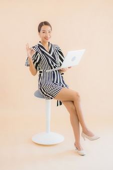 Портрет красивая молодая азиатская женщина с ноутбуком или компьютером
