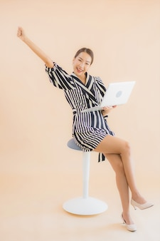 ラップトップまたはコンピューターと美しい若いアジア女性の肖像画