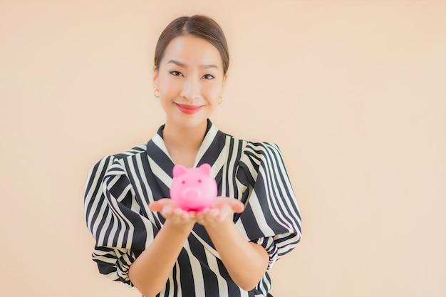 Женщина портрета красивая молодая азиатская с розовой копилкой