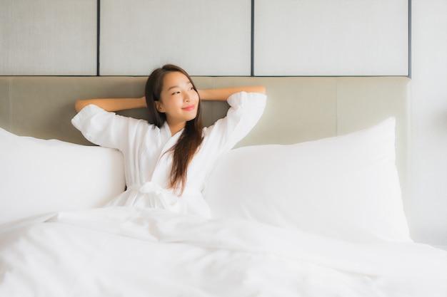 肖像画の美しい若いアジア女性は寝室で幸せな笑顔をリラックスします。
