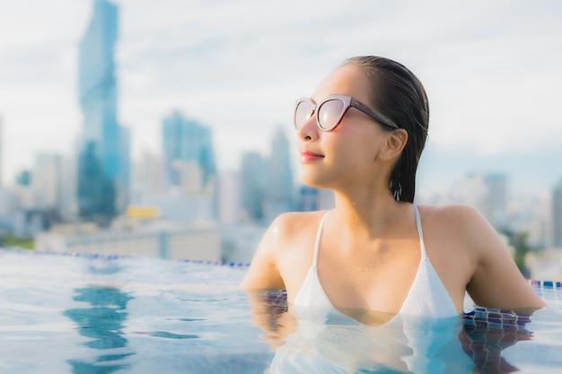 肖像画の美しい若いアジア女性は屋外スイミングプールの周りの幸せな笑顔レジャーをリラックスします。