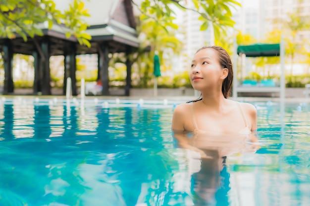 Женщина портрета красивая молодая азиатская ослабляет счастливый отдых улыбки вокруг открытого бассейна