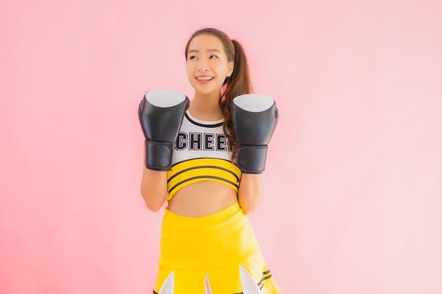 ボクシングアクションで肖像画の美しい若いアジア女性チアリーダー