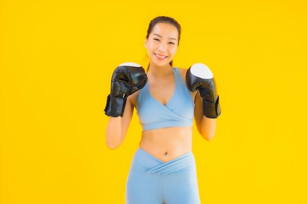 肖像画の美しい若いアジア女性は黄色のスポーツウェアを着用します。