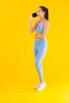 肖像画分離された黄色のスマート携帯電話を持つ美しい若いアジア女性