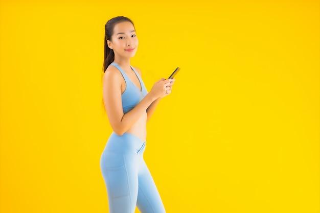Женщина портрета красивая молодая азиатская с умным изолированным мобильным телефоном на желтом цвете