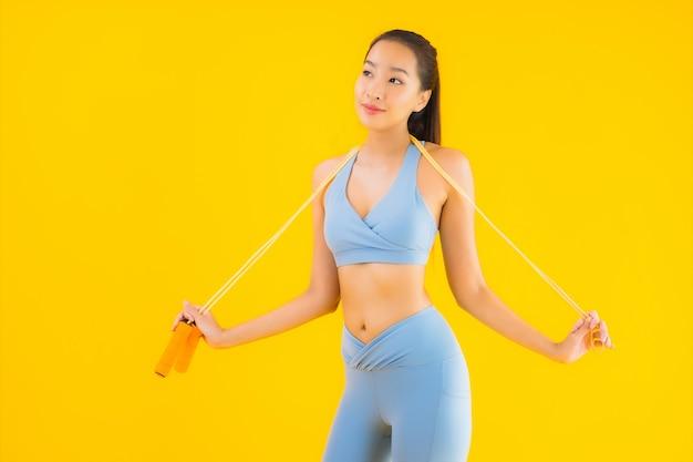 肖像画の美しい若いアジアの女性はロープでスポーツウェアを着用します。
