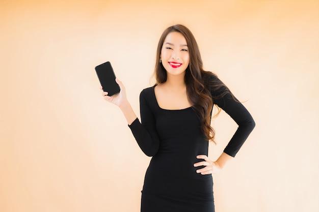 肖像画の美しい若いアジアの女性の笑顔幸せな使用スマート携帯電話