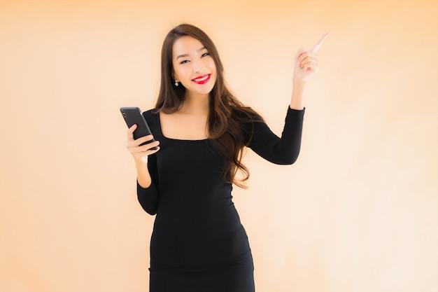 Портрет красивой молодой азиатской улыбки счастливой пользы женщины умный мобильный телефон