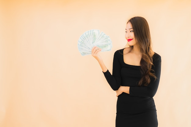 Улыбка женщины портрета красивая молодая азиатская счастливая с деньгами и наличными деньгами